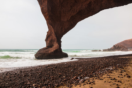 Coast, wave, beach and a large rock with arch
