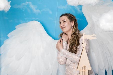 Lelijke vrouw in een witte jurk met witte vleugels probeert als engel te kijken