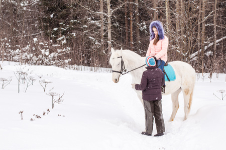 village man: Girl, horse trainer and white horse in a winter day
