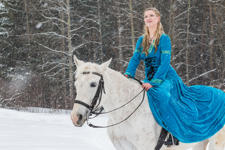 Woman in national dress and white horse in a forest in a winter day Stock Photo