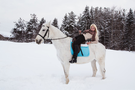 Nice girl and white horse outdoor in a winter day Zdjęcie Seryjne