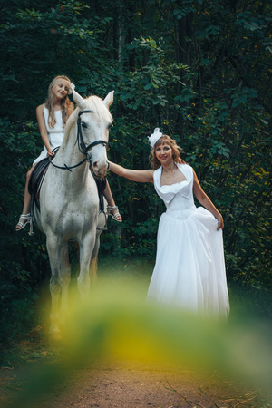 Bride, small girl and white horse in the park in a nice day