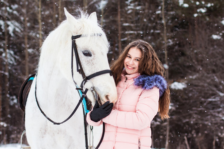 Nice girl and white horse outdoor in snowfall in a winter day Stock Photo