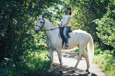 Girl and horse in the woods Stock Photo - 86189934