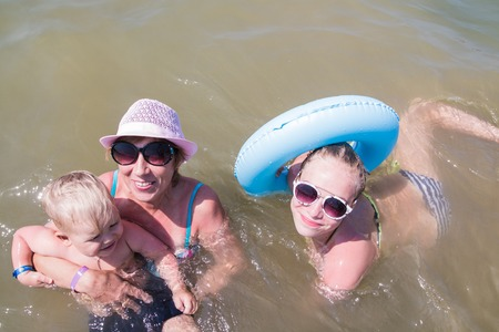 swimsuite: Grandmother, grandson and granddaughter swim in water in a swimsuite
