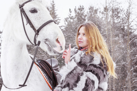 Nice girl and white horse outdoor in a winter day Stock Photo