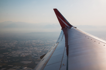 Wing of airplane flying above the Earth in the evening