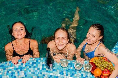 Three female friends in swimming-pool in the evening
