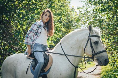 Meisjestiener en wit paard in een park in de zomer Stockfoto - 87962138