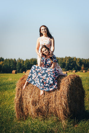 Mother and daughter in an autumn field with hay stack