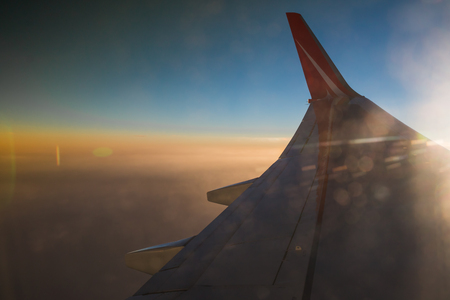 trip over: Wing of airplane flying above the Earth