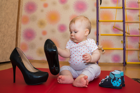Little girl and beautiful high-heeled shoes in the room Stock Photo