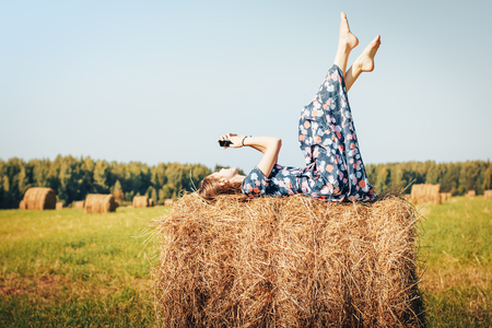 Teenager girl in an autumn field with hay stack Stock Photo
