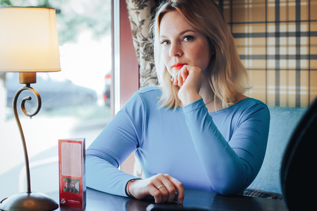 Blond woman in blue dress in cafe