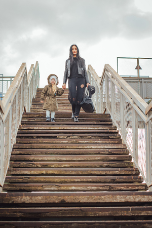 Beautiful small girl walk with mother on the stairs outdoors