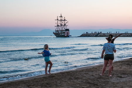 Side, Turkey - June 24, 2107: Photographer takes picture of model on the beach in the evening in Side city in Turkey