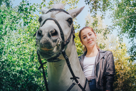 Girl teenager and white horse in a park in a summer day Stock Photo