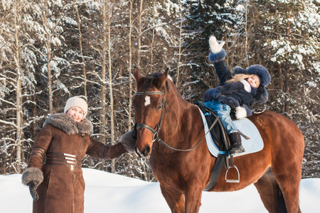 Small girl and mom near horse in a winter day