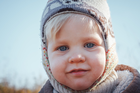 Happy baby boy outdoors with white hair in an autumn day Stock Photo