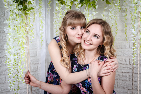 Two nice sisters with blond hair and flowers Stock Photo