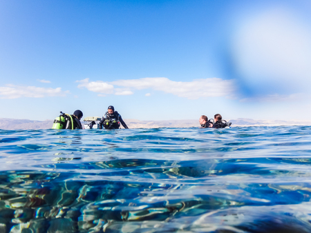 Jordan, Akaba - December, 25, 2017: Divers are preparing to dive in a blue water in sea