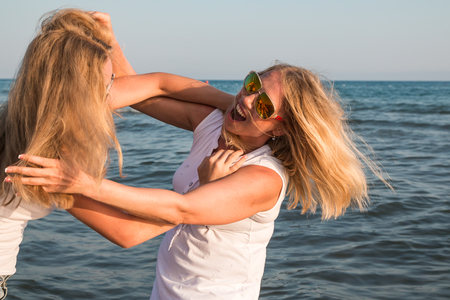 Zwei blonde Mädchen kämpfen in einem Wasser eines Meeres oder Ozean . Mutter und Tochter haben Spaß zusammen Standard-Bild - 93406485