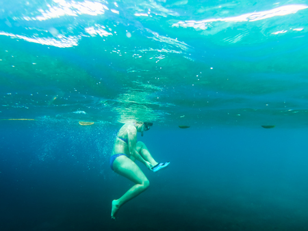 Swimmer under clear blue water while snorkeling