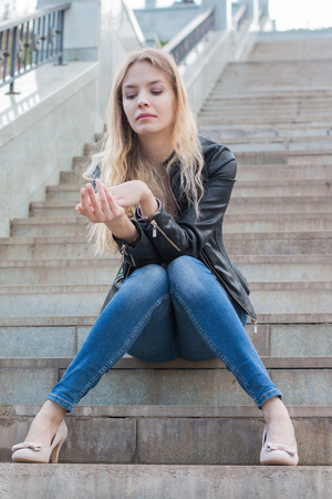 Girl with blond hair on the stone stairs
