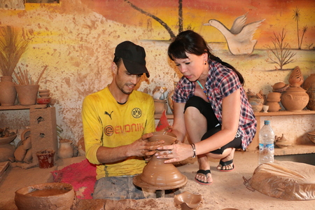 Agadir, Morocco - May 21, 2016: Man working on potter's wheel with raw clay with hands Editorial