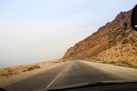 Desert highway and mountains through car window not far from Dead sea in Jordan Stock Photo