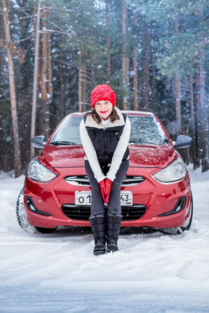 Girl in a red cap and warm jacket in the forest near red car in a winter day