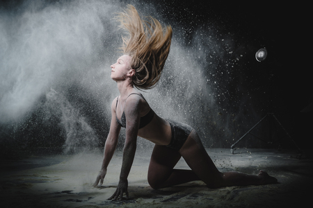 Girl dansing with flour during photoshoot on black background Imagens