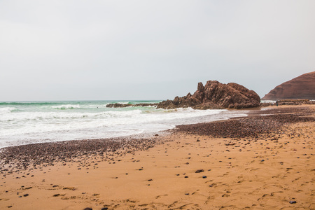 Coast, waves and beach with yellow sand and small pebbles Stock Photo