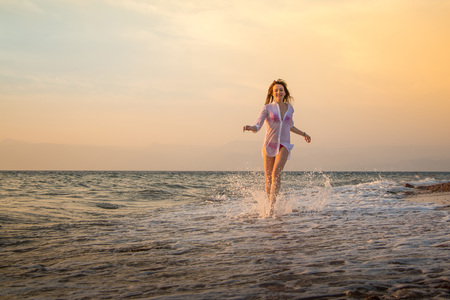 Girl rests and has fun in sea wave at sunset in the evening 写真素材