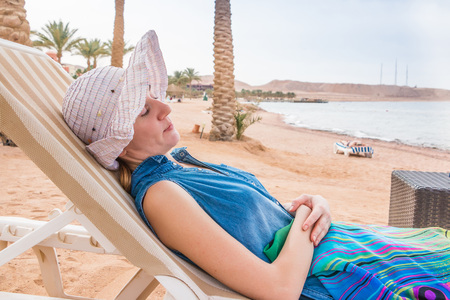 Blonde woman has rest on the beach on the sunbed in a summer day Imagens