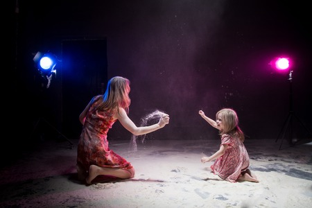 Young mother and small daughter during photoshoot with flour in dark studio