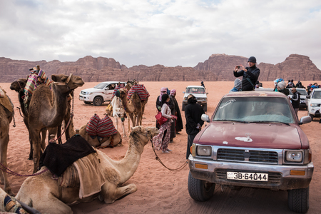 Wadi Rum, Jordan - December, 25, 2017: Tourists and Bedouins near camals in Wadi Rum desert in Jordan Editorial