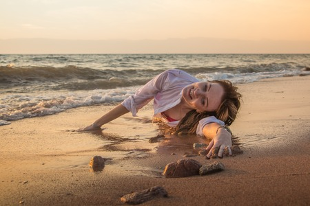 Girl rests and has fun in sea wave at sunset in the evening Banque d'images