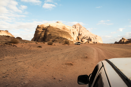 The view from the body of the jeep on beautiful views of sand and large rocks in the Wadi rum desert in Jordan on a evening just before sunset Stock Photo