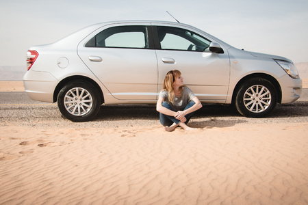 Girl have rest near car in desert in a summer day