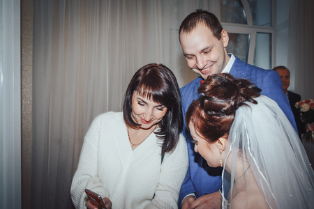 Russia, Kirov - November 24, 2017: Guest or relative congratulates bride and groom in the registry office after wedding registration in Kirov city in 2017