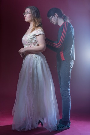 Young male assistant helps old actress to zip up white dress on stage with light of spotlight