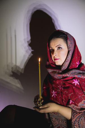 Portrait plump woman in red scarf with slim candle in her hand who is thinking about god and praying