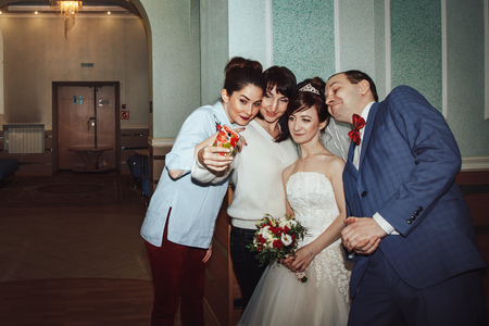 Russia, Kirov - November 24, 2017: Guests make selfie with bride and groom in the registry office after wedding registration in Kirov city in 2017