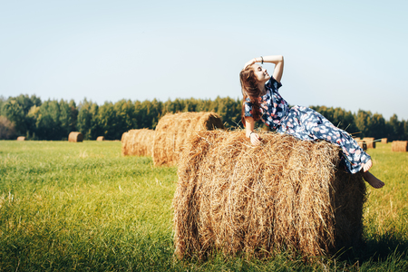 Teenager girl in a blue dress in an autumn field with hay stack