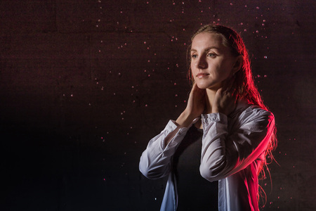Portrain of the girl in the white shirt with water drop in a dark room illuminated by light during a photoshoot with water in a small pool
