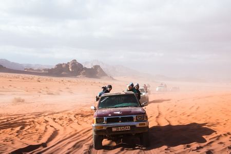 Wadi Rum, Jordan - December, 25, 2017: Bedouin's car jeeps and tourists in it in Wadi Rum desert in Jordan