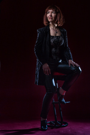 Confident ugly woman wearing black suit siting and posing in front of camera on stage with crimson floor and black background