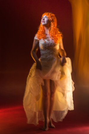 Old female actress with orange hair dancing in white dress with light show with yellow, orange and green lights around and red background Foto de archivo
