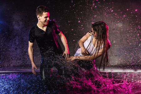 Couple young Teens together in small pool, drops of water and colored light behing them Stock Photo